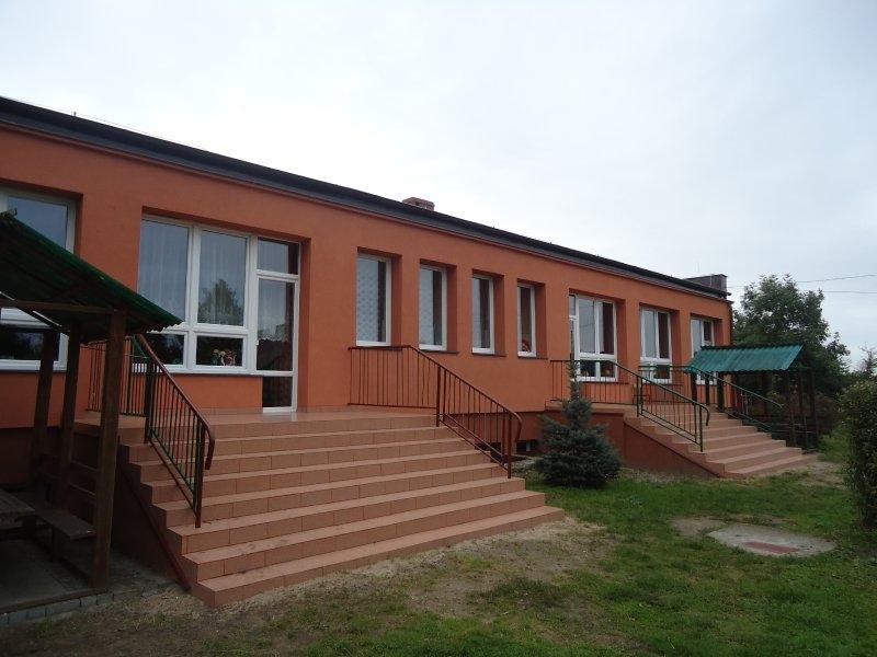Tył budynku przedszkola: docieplona elewacja w kolorze ceglastym, nowa stolarka okienno-drzwiowa