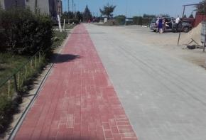 Ciąg pieszo-jezdny. Ciąg pieszy wykonany z czerwonej kostki brukowej, ciąg jezdny z szarej kostki brukowej