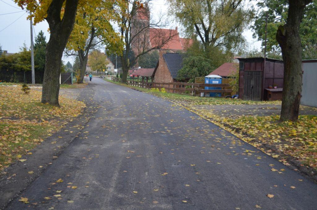 Nowa nawierzchnia bitumiczna na drodze w Lalkach. W tle kościół