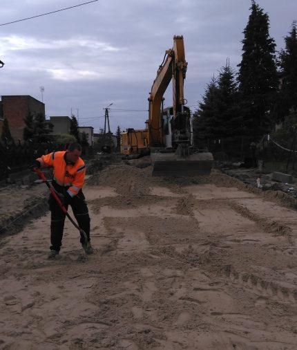 Pracownik budowlany oraz koparka rozprowadzający piasek pod nawierzchnię jezdni