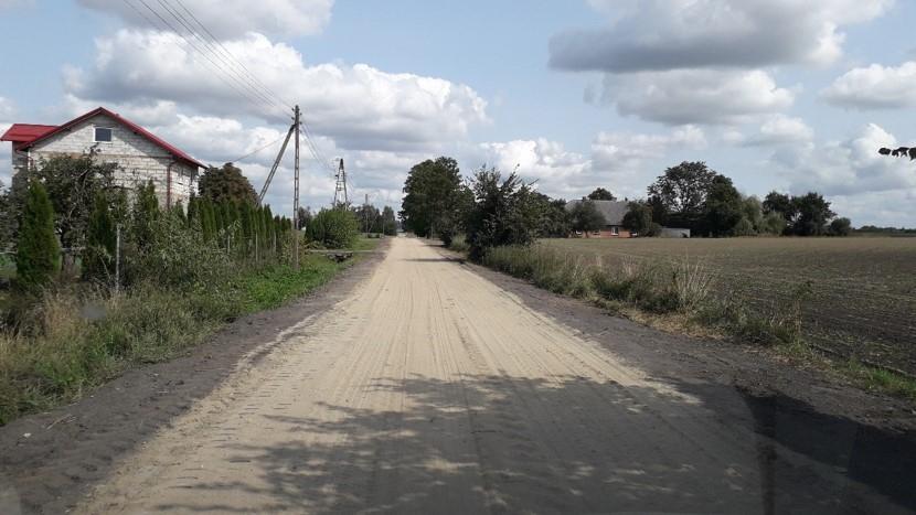 Droga z płyt jumbo prowadząca z pół uprawnych w stronę zabudowań mieszkalno-gospodarczych