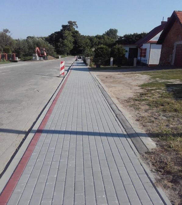 Wykonany ciąg chodnika z szarej kostki brukowej. W tle koparka realizująca prace po drugiej stronie jezdni