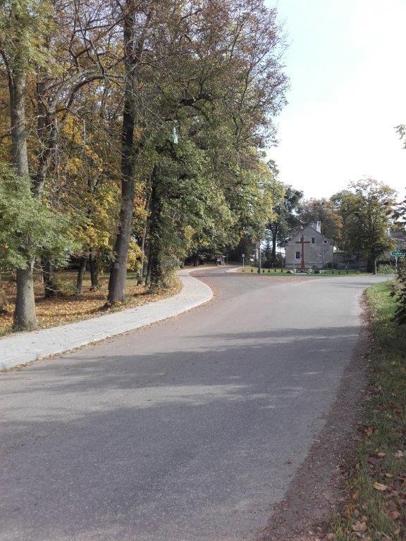 Droga przez Frącę, skrzyżowanie z drogą na Lalkowy. Po lewej park i nowy ciąg chodnika z kostki brukowej