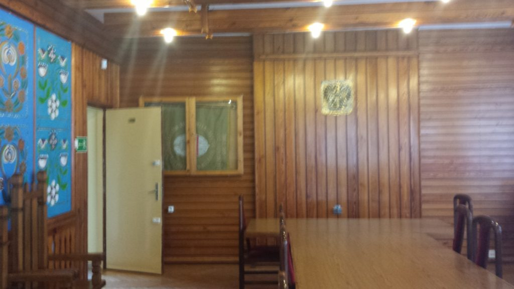 Sala ślubów przed remontem. Ściany wyłożone boazerią, po lewej wzory kociewskie o których mowa w tekście