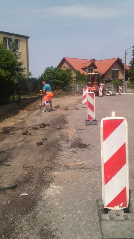Pobocze jezdni zabezpieczone słupkami ostrzegawczymi. W tle pracownik budowlany w trakcie realizacji prac przy pasie drogowym.