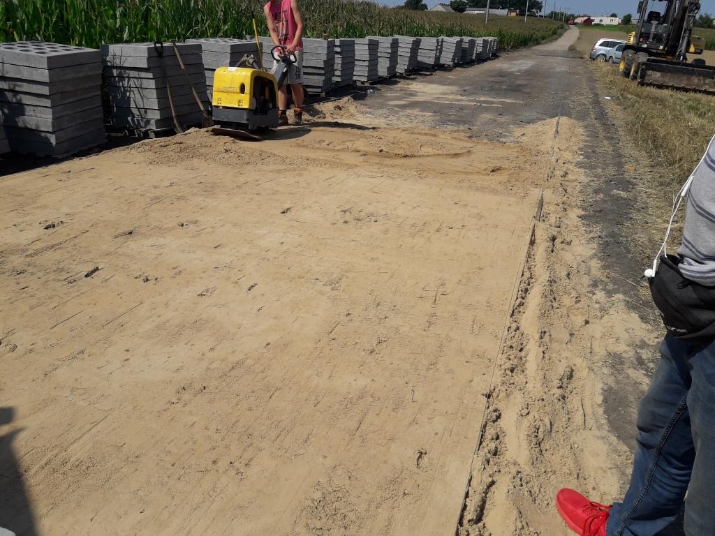 Pracownik budowlany utwardzający podkład pod płyty jumbo za pomocą zagęszczarki