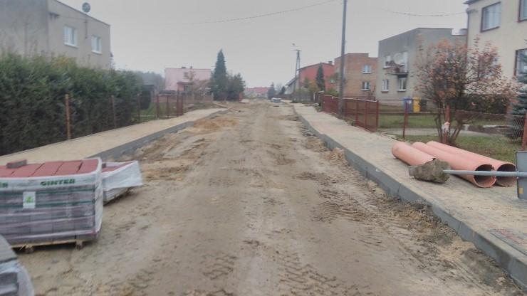 Nieutwardzona jezdnia, nowe chodniki wykonane z kostki brukowe, rury kanalizacyjne przed montażem