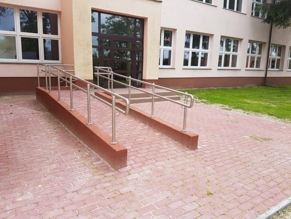 Podjazd do drzwi budynku ZKiW dla osób niepełnosprawnych wyłożony czerwoną kostką brukową