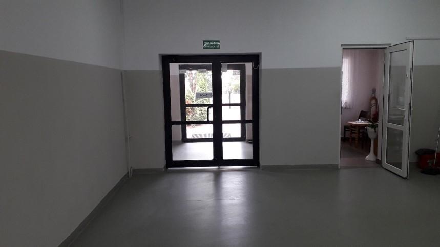Odnowione ściany przy wyjściu z budynku szkoły - biało-szare malowanie