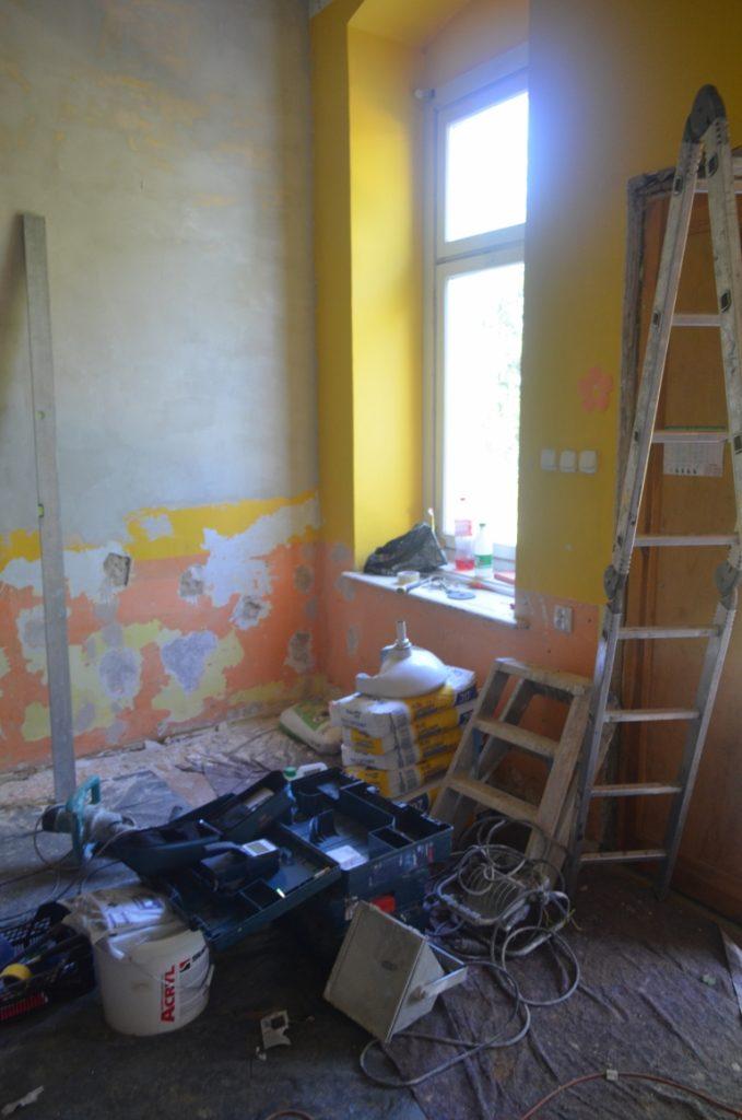 Ściany z częściowo zdrapną farbą, narzędzia, drabina