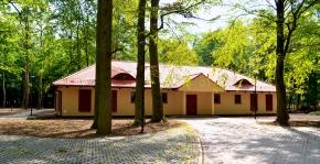 Parterowy budynek ulokowany w parku. Do budynku prowadzi droga z kostki brukowej.