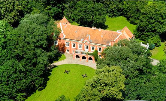 Neogotycki pałac w kolorze ceglastym, otoczony drzewami liściastymi. Przed budynkiem zadbany trawnik.